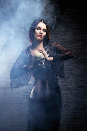 dungeon: Halloween concept: young and sexy witch makes the witchcraft in the dungeon