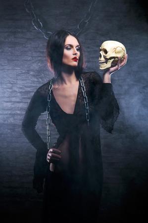 Halloween-concept: jonge en sexy heks maakt de hekserij in de kerker Stockfoto