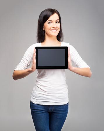 jolie fille: Jeune et belle fille adolescente tenant un tablet pc ipad dans ses bras sur fond gris Banque d'images