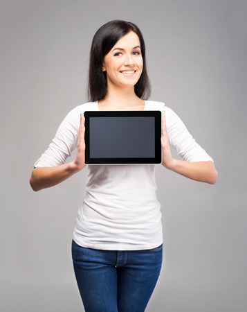 pretty girl: Young and beautiful teenager girl holding an ipad tablet pc in her arms over grey background