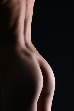 nackte schwarze frau: Schönen Arsch der jungen Frau auf einem dunklen Hintergrund Lizenzfreie Bilder