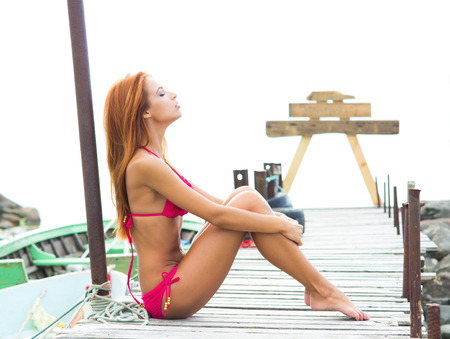 Young sexy woman in swimsuit relaxing on the pier