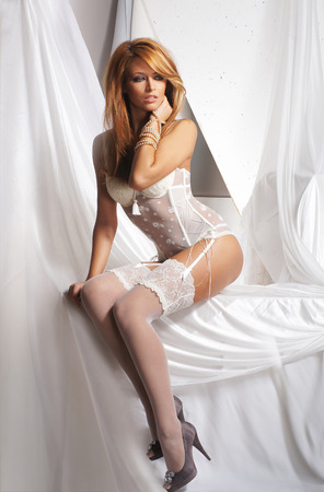 beautiful redhead: Young and sexy redhead woman in white lingerie Stock Photo