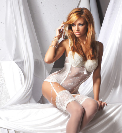Young and sexy redhead woman in white lingerie Stock Photo