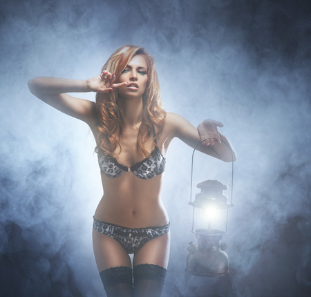 ancient sexy: Young and beautiful woman with the vintage lamp over smoky background