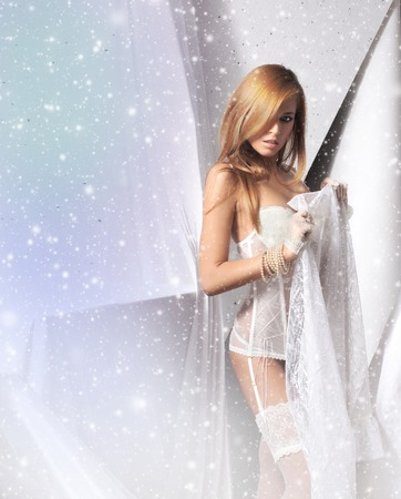 Young and sexy redhead woman in white lingerie over snowy background Stockfoto
