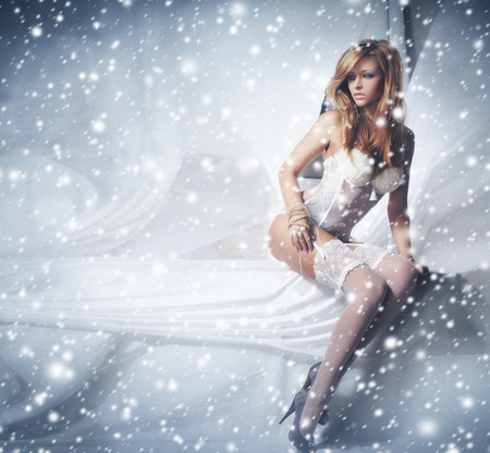 sexy bride: Young and sexy redhead woman in white lingerie over the winter background with the snow