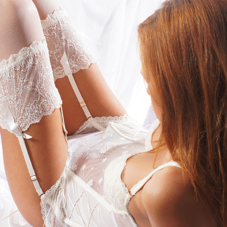 Fashion image of young and sexy redhead woman in white lingerie Stock Photo
