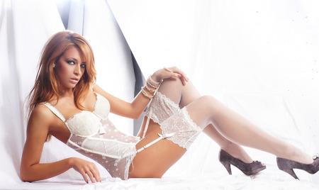 sexy beine: Junge und reizvolle Redheadfrau in der weißen Wäsche