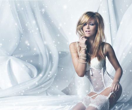 Young and sexy woman in white lingerie over a winter background with a snow