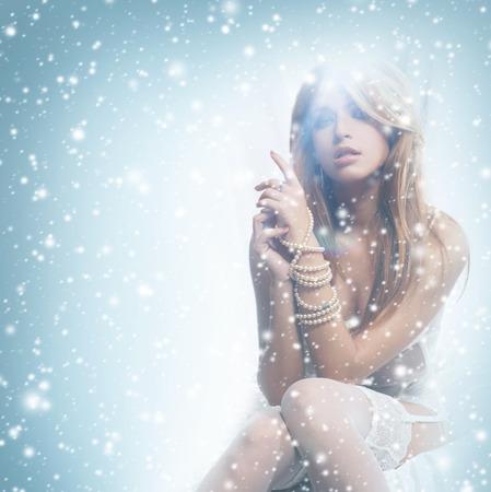 pelirrojas: Mujer pelirroja joven y sexy en ropa interior blanca sobre el fondo de invierno con la nieve