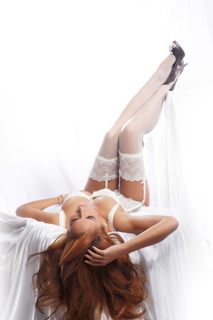 Young and sexy redhead woman in white lingerie Standard-Bild