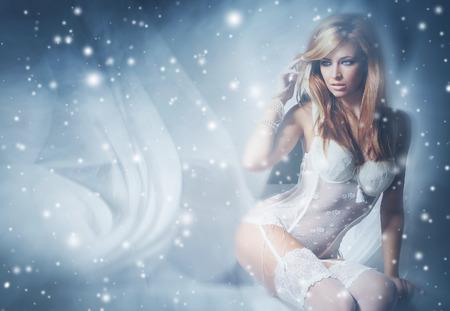 sexy beine: Junge und reizvolle Frau in wei�en Dessous �ber einen Winter Hintergrund mit einem Schnee