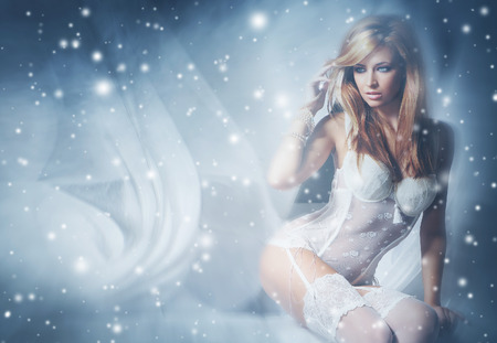 sexy women body: Young and sexy woman in white lingerie over a winter background with a snow