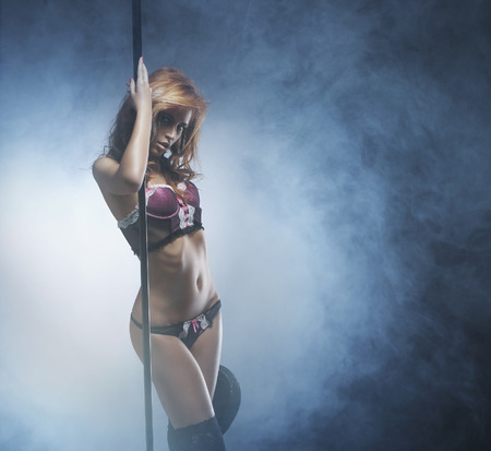 girl undressing: Beautiful and sexy striptease dancer over the smoky background Stock Photo
