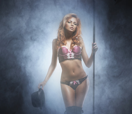 strip dance: Young and beautiful redhead strip dancer in lingerie over smoky background Stock Photo
