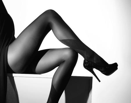 piernas sexys: Foto blanco y negro de las hermosas piernas en medias bonitas sobre fondo blanco
