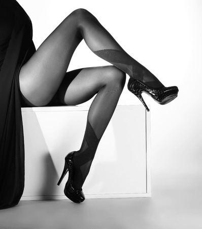 Black and white photo of the beautiful legs in nice stockings over white background