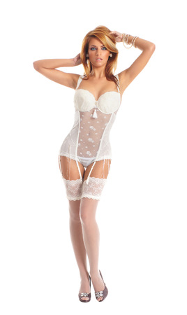 Young and sexy redhead woman in white lingerie isolated on white