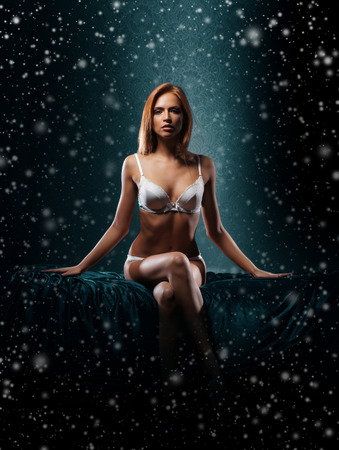 Sexy girl in underwear over the Christmas background with a snowflakes Stock Photo