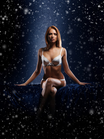 nu: Young and beautiful woman in sexy lingerie over the snowy winter background Stock Photo