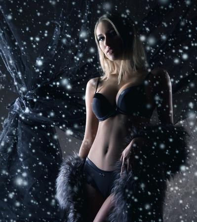 Young and beautiful woman in lingerie over the snowy winter background