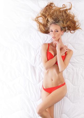 naked young women: Молодая сексуальная девушка в эротическом красном белье на белом фоне Фото со стока