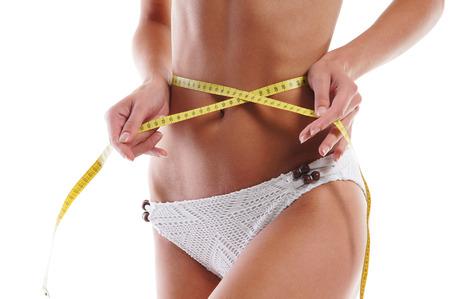 femme en sous vetements: Jeune femme séduisante mesure son corps isolé sur blanc