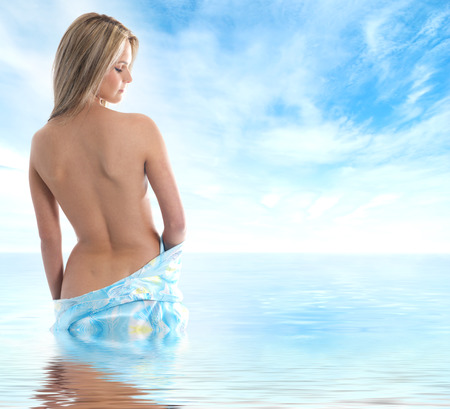 naked woman back: Young sexy blond in sari over sky and sea background