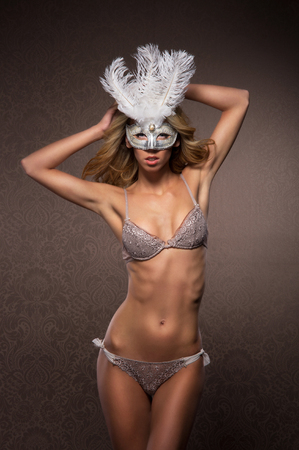 Young sexy woman in erotic lingerie and mask over the luxury background