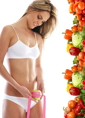 belly pepper: Young and sexy blond measuring her waist isolated over white background Stock Photo