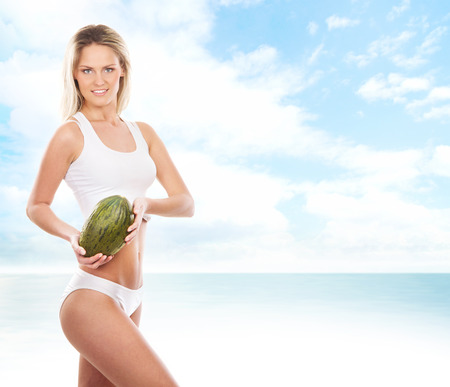 heaven background: Young sexy woman in sporty clothes with a melon over the heaven background Stock Photo