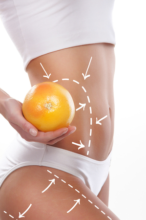 with orange and white body: Female body with the drawing arrows on it isolated on white. Woman holding orange or grapefruit. Fat lose, liposuction and cellulite removal concept. Stock Photo