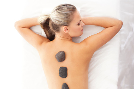 hot stone: Young attractive woman getting hot stone treatment over white background