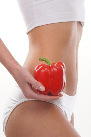 belly pepper: Dieting concept, Beautiful belly and a fruit isolated on white
