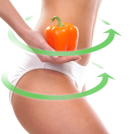 belly pepper: Dieting concept. Beautiful belly, green arrows and a pepper isolated on white.
