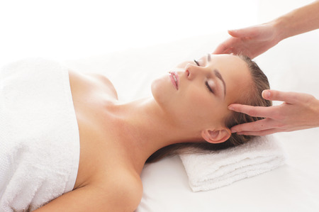 healing energy healer: Young attractive woman getting massaging treatment over white background
