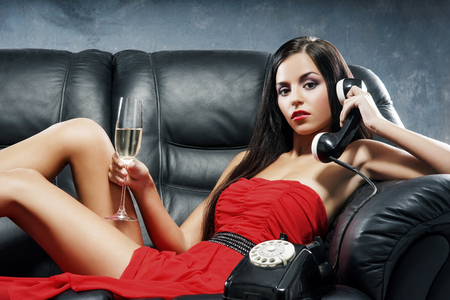 Young, beautiful and glamour woman in red dress with the vintage telephone on the leather sofa