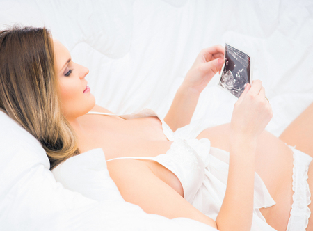expectant arms: A young and pregnant woman relaxing in the bed and holding an ultrasound