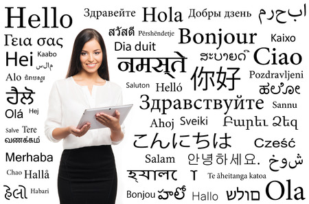 Young attractive woman with and ipad over the background with a different world languages (language school concept)