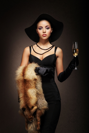 black dress: Attractive young lady with the glass of sparkling wine over the retro background