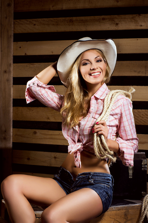 sexy cowgirl: Young, happy and sexy cowgirl in western style