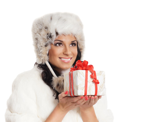 Young and beautiful woman holding a nice Christmas present over white background