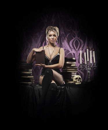 Beautiful and sexy witch in sexy lingerie posing in gothic interior