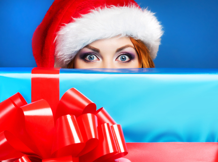 'hide out': Young and beautiful girl with the Christmas present over blue background Stock Photo