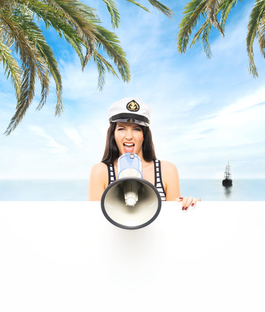 sailor girl: Young, beautiful and sexy sailor girl with a megaphone over sea and sky background