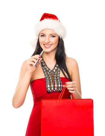 christmas shopper: Young and beautiful Christmas shopper girl with the electronic cigarette isolated on white background Stock Photo
