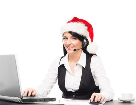 Young, confident and beautiful support operator in Christmas hat working in a call center Stockfoto