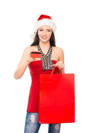christmas shopper: Young and beautiful Christmas shopper girl with the credit card isolated on white background
