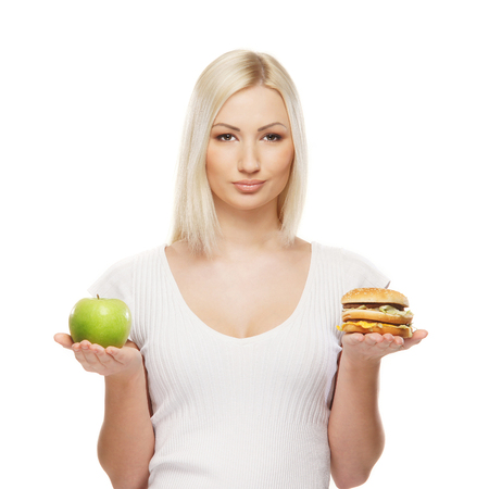 harmful: Young attractive girl making choice between healthy and harmful food